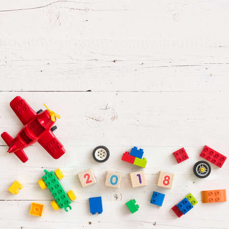 Closeup of multi-colored bricks and toys from plastic. Wooden cubes with numbers 2018 on old wooden background. Early learning. Educational toys