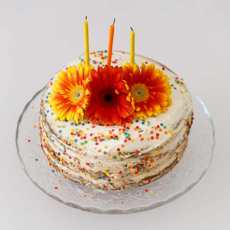 Closeup of cream cake on glass dish. Homemade cake decorated with multicolored flowers and candles. Symbol of Birthday.
