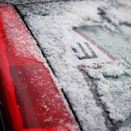 Closeup of car sticker with a Russian letter denoting spikes on a cars snow-covered rear window. The sign warns drivers that car is equipped with spiked wheels. Safe movement on icy roads in winter
