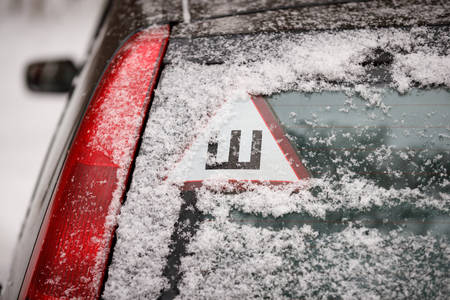 The first snow on the car and on the streets. Warning sign -spikes- for cars with winter tires with spikes. Studded tire season. Safe movement on icy roads in winter
