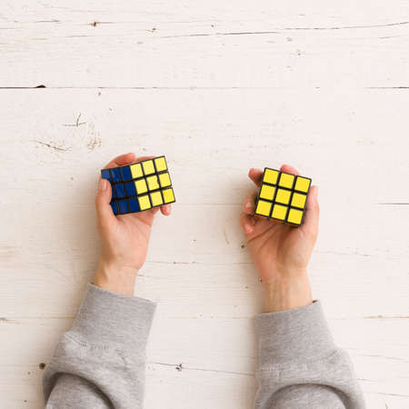 Moscow, Russia, February 16 2018: Rubik's cube in woman's hands, closeup, white wooden background. Girl holding Rubik's cube and playing with it. Editorial