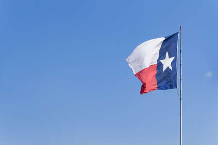 Texas flag waving on the wind on blue sky. State Flag of Texas on a Windy Day