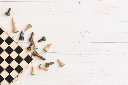 Top view on wooden chess board and chess figures on white wooden table background