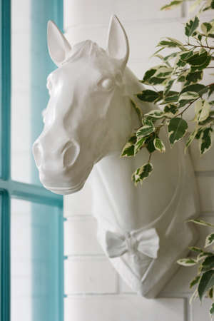 Sculpture of a horse's head with a bow tie is mounted directly on the wall. Stylish Interior Decor Concept