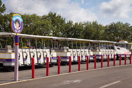 Florida, USA, May 23, 2013: Special transport, shuttle, tram in Disneyland awaiting guests in the parking lot. Transfer guests amusement park with parking to the entrance to the park.