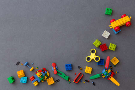 Multicolored plastic cubes on a gray background. Yellow spiner between cubes. Toys and other equipment for the early development of the child.