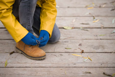 Closeup of cute kid boy tying laces while walking in the city park on a cold autumn day. A child learns to tie shoelaces