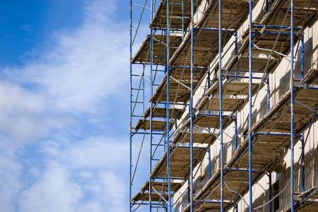 Ponteggio vicino a una nuova casa in costruzione come struttura edilizia di supporto temporanea durante la costruzione contro il cielo blu. Archivio Fotografico