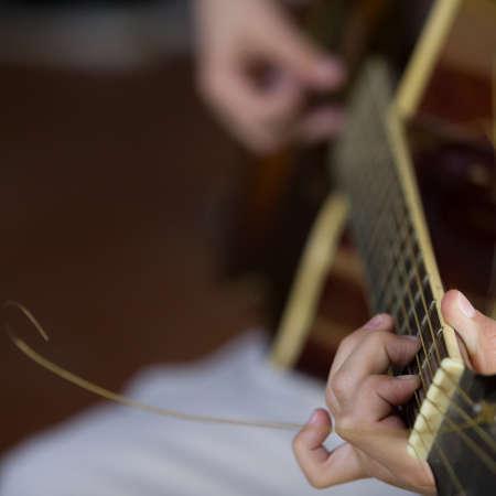 Closeup of musicians hands playing guitar at a concert. Reklamní fotografie