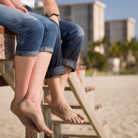 Closeup of legs of a young woman and a man. The girl and the guy are sitting on the rescue tower on the ocean beach. Positive and good mood for the whole day.