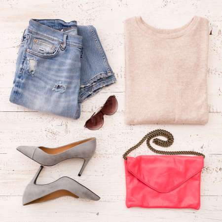 Close-up of fashionable women's accessories: jacket, jeans, shoes, leather clutch and other accessories on a white wooden table