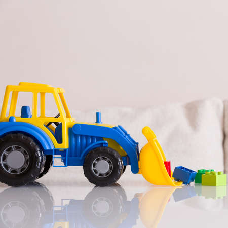 Bright color toy bulldozer on a white table. Multi-colored tractor collects cubes in the bucket. Early development. Kids toys