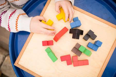Vue de dessus des mains de l'enfant ramassant un puzzle cubique. Chiffres multicolores du puzzle de cubes en bois. Développement précoce. Banque d'images