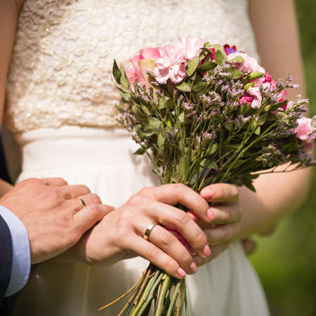Closeup hands of newlyweds with wedding rings and bridal bouquet. Family life.