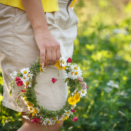 Closeup of a girl holding a wreath of wild flowers. The girl walks in the park with a wreath in her hands. Spring in the park