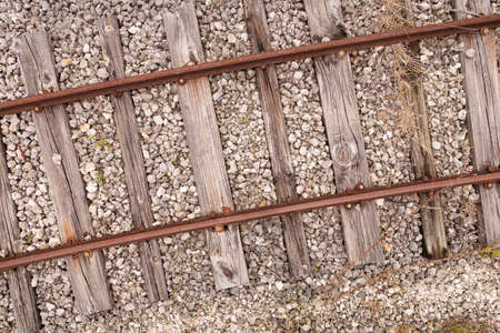 Old rusty rails on cracked wooden sleepers sprinkled with small stones. Top view of the vintage railway tracks. Closeup of part of the way