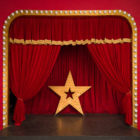 Improvised theatrical stage with a red velvet curtain and a big star with luminous lights. Concert hall. Star performance