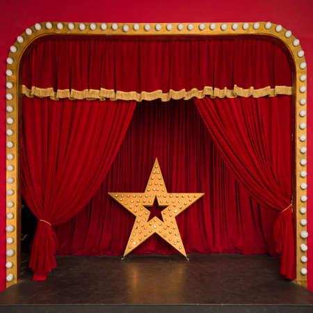 Improvisierte Theaterbühne mit rotem Samtvorhang und einem großen Stern mit leuchtenden Lichtern. Konzerthalle. Starleistung Standard-Bild