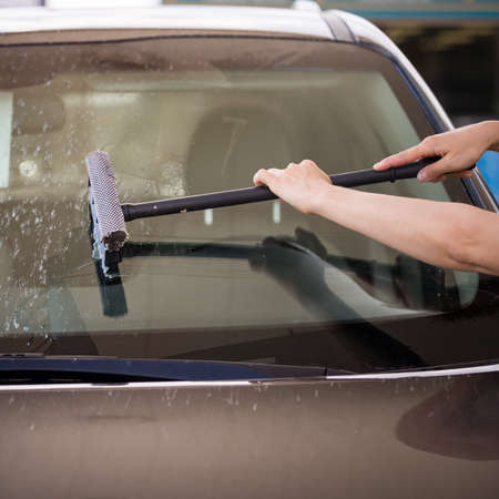 A girl with a brush in her hands washes the windshield of the car from a large number of dead insects. The season of flying insects. Flying insects covered the windshield, bumper and hood.