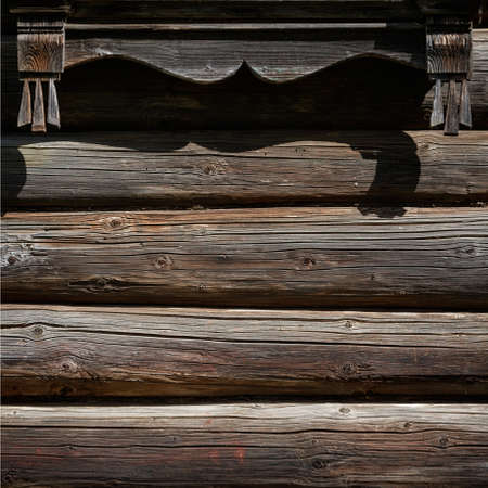 Fragment of the old log wall of a wooden house. Very old house in the village. Dry dark logs of a rural house. Standard-Bild