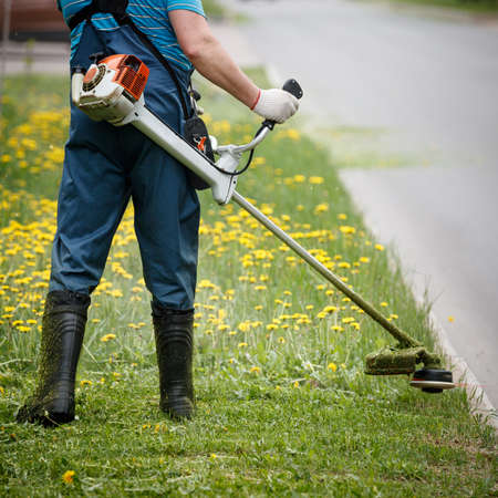 Closeup of a worker in special reflective clothing with a gasoline mower in hand. Man mows the grass with dandelions on the lawn with trimmer