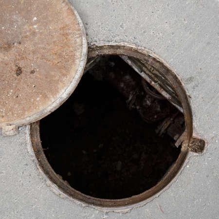 Primo piano di un tombino aperto con una copertura sulla strada asfaltata. Vista dall'alto della fogna. Pericolo per le persone. Riparazione di condotte sotterranee. Archivio Fotografico