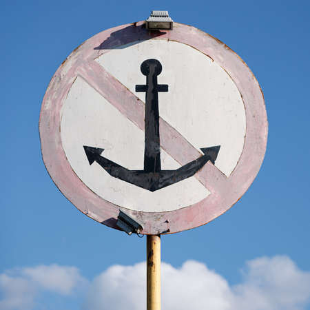 Closeup of a special mark for ships. Parking in this place is prohibited. Crossed anchor in a circle.