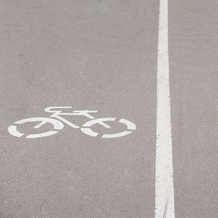 Close-up of a dedicated lane on an asphalt road with a painted bicycle sign. A white line separates the cycling and pedestrian paths. Safety on the road. Ecological transport