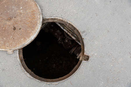 Top view of the dangerous open sewer manhole, a danger to people who walk along the street in the city. The cover lies next to the hatch. Repair of the pipeline under the ground.