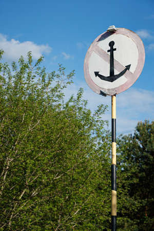 Special sign with crossed anchor for ships on the background of trees. Parking in this place is prohibited.