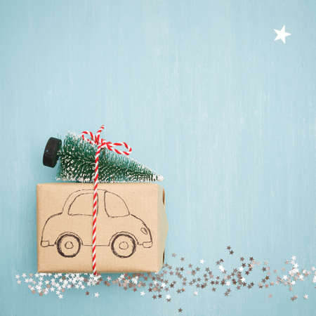Closeup of a gift on a blue background. The gift is packed in craft paper with a painted car. A car with a Christmas tree on the roof rides along a path of silver stars. Festive concept. Stock Photo