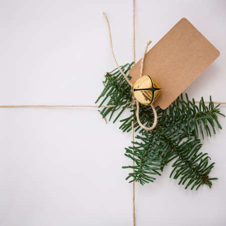 Closeup of a Christmas or New Year's gift decorated with a bell, tag and fir branch. A gift wrapped in Christmas stylish paper lies on a white wooden table. Festive and Christmas concept