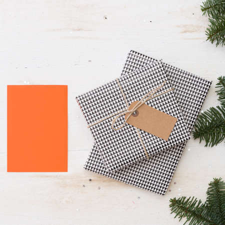 Closeup of gift boxes wrapped in paper and decorated with ribbon and tag. Gifts for the New Year or Christmas on a white wooden table surrounded by fir branches. Blank orange greeting card for text. Stock Photo