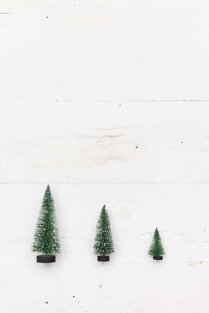 Top view on three little Christmas trees on white wooden background. Holidays and winter concept. Stockfoto