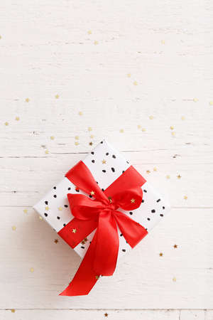 Closeup of a stylish birthday or christmas gift. Top view of a beautiful gift tied with a red gift ribbon on a white wooden table background covered with gold stars. Festive concept Stock Photo
