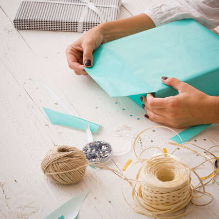 Closeup of a young womans hands wrapping a festive gift for a birthday or for any other event. Ribbons, stars, paper, scissors and a gift lie on a white wooden table. ?oliday concept