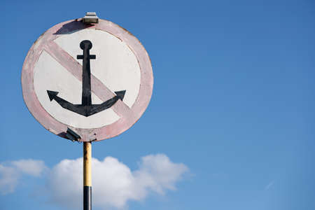 An old sign for ships indicating a parking ban in this place. Sign, do not throw anchors, against the blue sky.