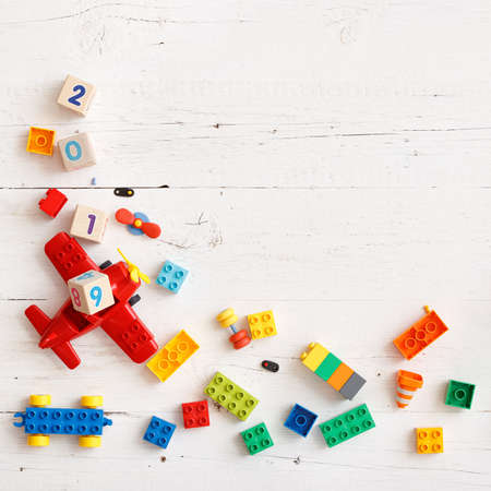 Closeup of wooden cubes with numbers 2018, 2019 year. Top view on childrens educational toys, multi-colored cubes, bricks and other details on a white wooden background.