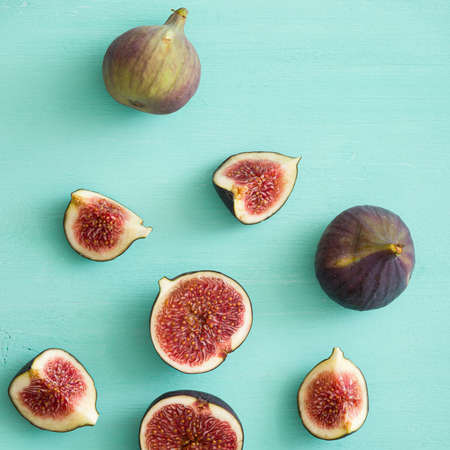Closeup of fig fruits lying on the table. Whole and sliced fig fruits on a turquoise background.