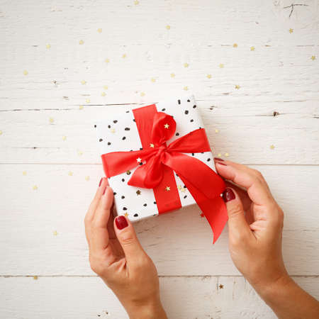 Closeup of a stylish birthday or christmas gift with the hands of a young woman. Top view on a beautiful gift tied with a red gift ribbon on a white wooden table background. Festive concept