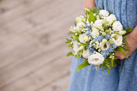 Closeup of a girl in a blue dress with a bouquet of white roses in her hands. A young woman is holding a beautiful wedding bouquet. Bride 스톡 콘텐츠