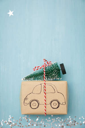 A gift wrapped in craft paper with a painted car carries a Christmas fir tree on the roof, along a path of silver stars. Festive, new year or christmas concept.