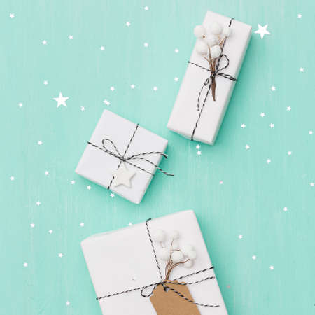 Closeup on gifts wrapped in white paper and decorated with Christmas decorations. Gifts lie on a turquoise wooden background covered with silver stars. Holiday and Christmas concept