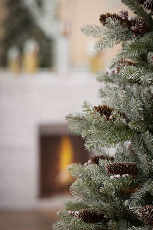 Closeup of a Christmas fir tree with cones. Artificial Christmas tree with natural cones set at home for the celebration of Christmas or the New Year. Festive atmosphere. Holiday concept