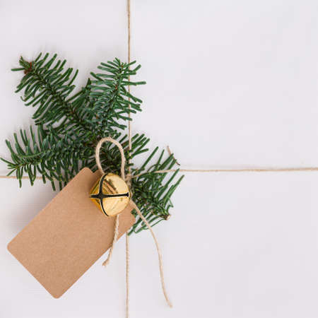 Closeup of a gift for Christmas or New Year. The gift is packed in white paper and decorated with a bell, a tag and a fir branch. View from above