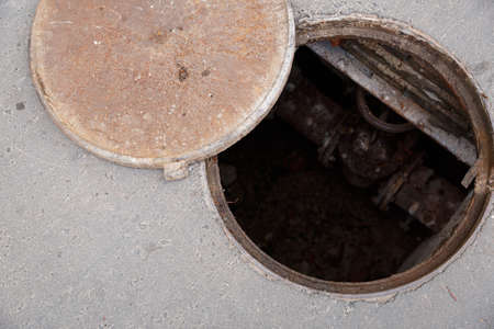 Open hatch with cover on the asphalt road. Top view of the sewer. Danger to people. Underground pipeline repair.
