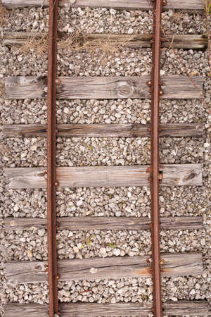 Top view of the old rusty rails with cracked wooden sleepers with a mound of small stones. Old vintage railway tracks