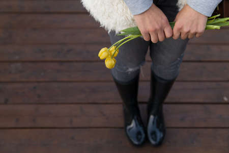 Girls hands holding a bunch of flowers tulips. A young woman in rubber boots and a warm sweater with flowers are standing on a wooden walkway after the rain. 스톡 콘텐츠