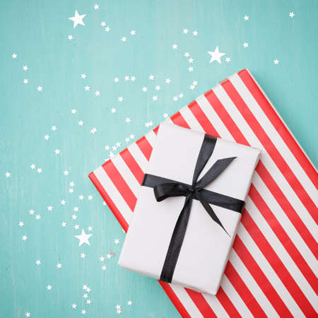 Closeup on gifts wrapped in white and striped red paper with black ribbon. Gifts lie on a turquoise wooden background covered with silver stars. Stylish holiday and christmas concept