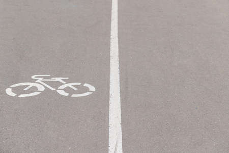 A dedicated lane on an asphalt road with a special bicycle sign. Cycle path divided by a white line with a pedestrian road. Safety on the road. Environmentally friendly transport